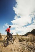 Biker standing with bicycle on dirt road at mountain Stock Photos