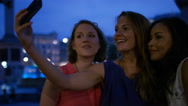 Three female friends take a photo together in the city at night Stock Footage