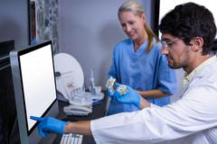 Dentist and dental assistant using a computer while working on mouth model Stock Photos
