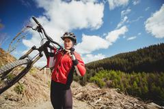 Biker carrying bicycle on mountain against sky Stock Photos