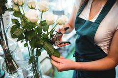Mid section of female florist trimming flower leaf at her flower shop Stock Photos