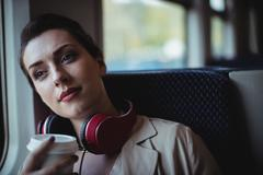 Thoughtful beautiful woman holding disposable cup in train Stock Photos