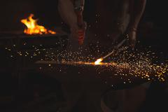 Blacksmith working on a heated iron rod in workshop Stock Photos