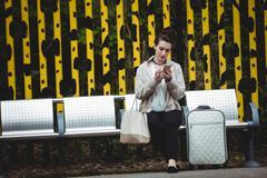 Woman using mobile phone at railroad station platform Stock Photos