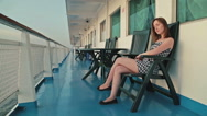 Woman sitting on deck of cruise ship Stock Footage