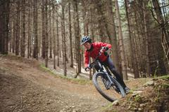 Mountain biker riding on dirt road amidst tree in forest Stock Photos