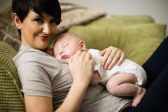 Close-up of baby sleeping on her mother in living room at home Stock Photos