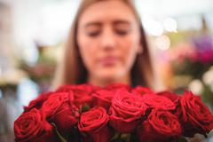 Female florist holding bunch of rose flowers in the flower shop Stock Photos