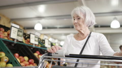 4K Senior lady with shopping cart buying groceries in the supermarket Stock Footage