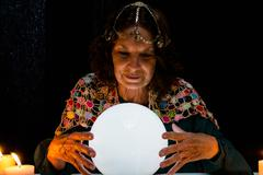 Smiling mature fortune teller with crystal ball Stock Photos