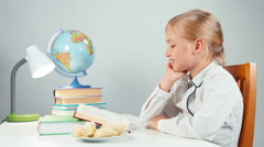 Schoolgirl eating potato chips and reading textbook at the table Stock Footage