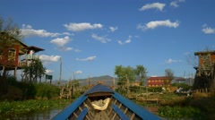 Boat going through traditional floating village, Inle Lake, Myanmar Stock Footage