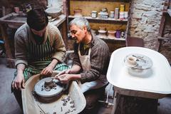 Craftsman discussing with man working in workshop Stock Photos