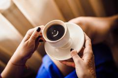 Morning coffee. Woman holds a white coffee cup Stock Photos