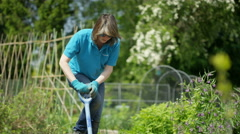 4K Woman working in community garden as part of a volunteer project Stock Footage