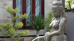 Water flowing from woman sculpture in the garden of balinese house Stock Footage