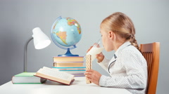 Portrait blonde school girl 7-8 years reading book drinking milk and eating Stock Footage