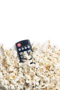 Tasty popcorn and tv remote control. Stock Photos