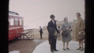 1967: vacationing people talking and waiting to board large red tour bus  Stock Footage