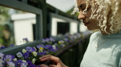 4K Volunteers working in community garden, woman tending flowers in a planter Stock Footage