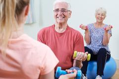 Seniors At Fitness Class With Instructor Stock Photos