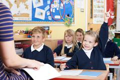 Class Of Elementary School Pupils Answering Question Stock Photos
