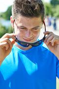 Close Up Of Young Man Running In Park Putting On Sunglasses Stock Photos