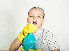 Smiling little housewife washed the window with a cloth and detergent. Large Stock Photos