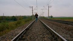 Man runs on railroad tracks Stock Footage