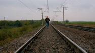 Man runs on railroad tracks Stock Footage