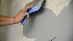 Workman plastering with a spatula wall Stock Footage