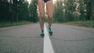 Athletic youg woman Jogging in a park. Close up of running shoes and legs in Stock Footage