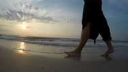 4K resolution footage: barefoot legs of young female walking on the sunset beach Stock Footage