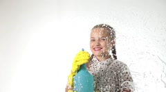 Smiling little housewife washed the window with a spray, cloth and detergent Stock Footage