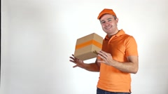 Delivery man in orange uniform tossing a small parcel. Light gray backround Stock Footage