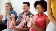 Happy friends with popcorn watching tv at home Stock Footage