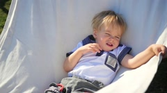 The beautiful little child relaxes in hammock Stock Footage