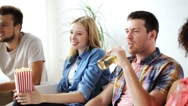 Friends with popcorn and beer watching tv at home Stock Footage