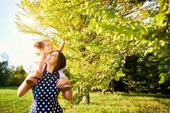 Mum with a daughter on his shoulders on the nature of play, walk happy, smili Stock Photos