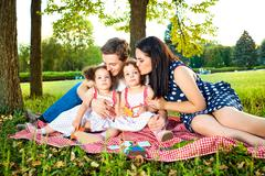 Happy family in the park summer, autumn. Parents and two daughters sitting, p Stock Photos
