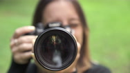 Young photographer woman pointing the lens at the camera Stock Footage