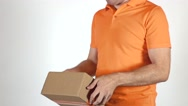 Courier in orange uniform tossing a small parcel. Light gray backround, Super Stock Footage