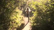 Girl running through the park in the sunshine Stock Footage