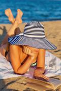 Young woman with hat reading book on sea beach lying on the sand. The concept Stock Photos