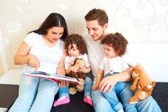 Girls twins with parents read book on the sofa in the room. A happy family. M Stock Photos
