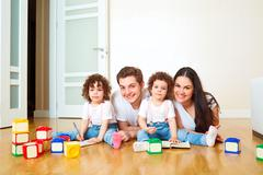 Portrait of a happy family on the floor, playing with cubes. Mother, father a Stock Photos