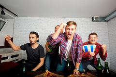 Friends sprot watching on TV, have fun, eat pizza. Friends to eat pizza, drin Stock Photos
