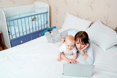 Mother with baby on the bed looking at a laptop with enthusiasm in the childr Stock Photos