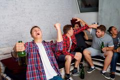 Friends cheering for your team together. Concept sports fans. Friends drink b Stock Photos