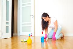 A woman in a room of the house cleaning the floor in rubber gloves. Mom makes Stock Photos